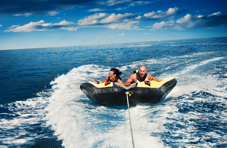 A couple riding on the inflatable tow tube on a speed